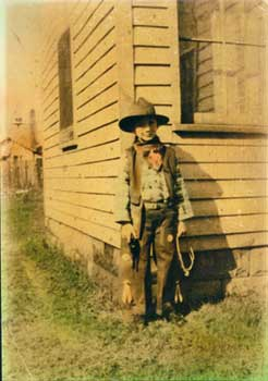 Sepia photo of a young boy in cowboy attire next to a house