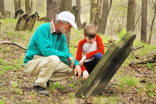 Older man and a younger boy in a wooded area with a tilted gravestone.