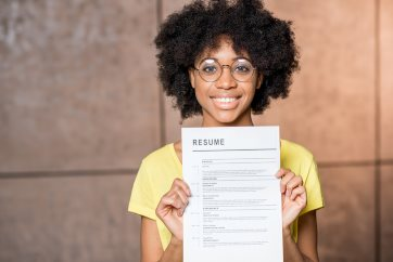 Photo of an woman in a yellow shirt holding a piece of paper with the text Resume at the top