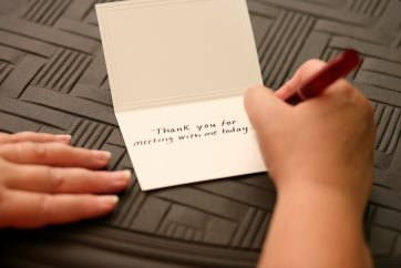 A hand writing the words Thank You For Meeting With Me on a s